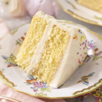 A moist and delicious slice of Vanilla Cake on a porcelain plate.