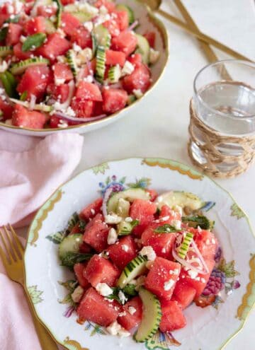 A plate of watermelon salad beside a glass of water and a bowl of watermelon salad.