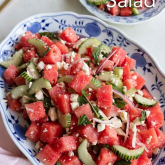 Pinterest graphic of an oval platter of watermelon salad with a small plate beside it.