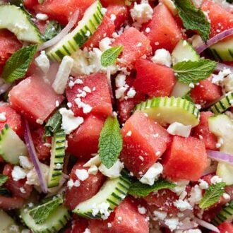 Close up of a watermelon salad with cubed watermelon, cucumbers, onions, feta, and mint.