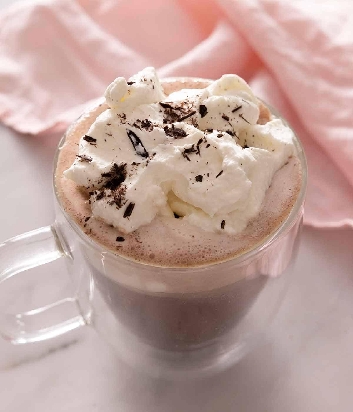 A cup of hot chocolate with whipped cream on top and chocolate shavings.