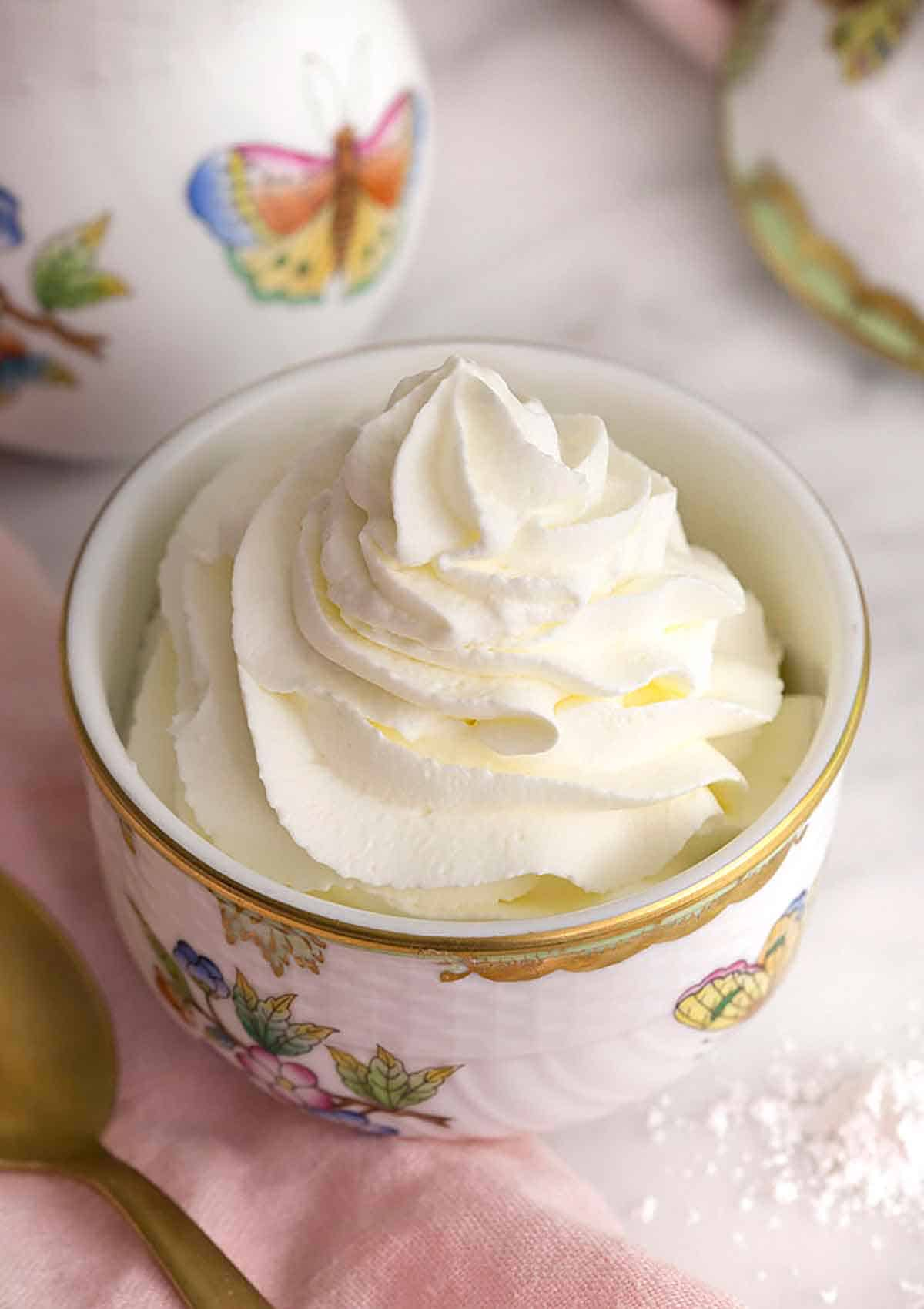 A bowl with flowers and butterflies containing whipped cream.