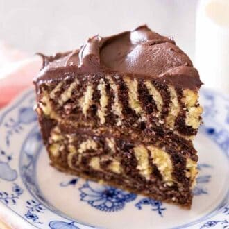 Close up of a slice of zebra cake with chocolate frosting on a blue and white plate.