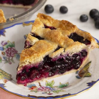 A piece of blueberry pie with a lattice top on a white plate next to some blueberries.