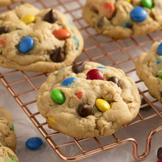Monster Cookies with M&Ms on top cooling on a copper rack.