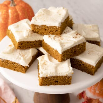A stack of pumpkin bars with cream cheese frosting on a cake stand.