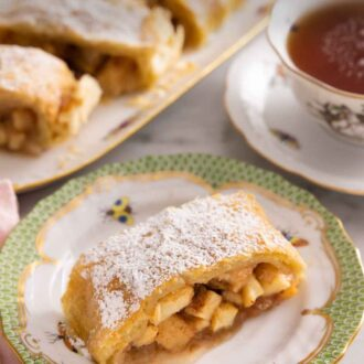 Pinterest graphic of a plate with a serving of apple strudel on it with the platter in the background, out of focus.