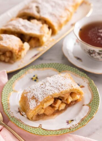 A serving of apple strudel on a plate in front of a cup of tea and more sliced apple strudel pieces.