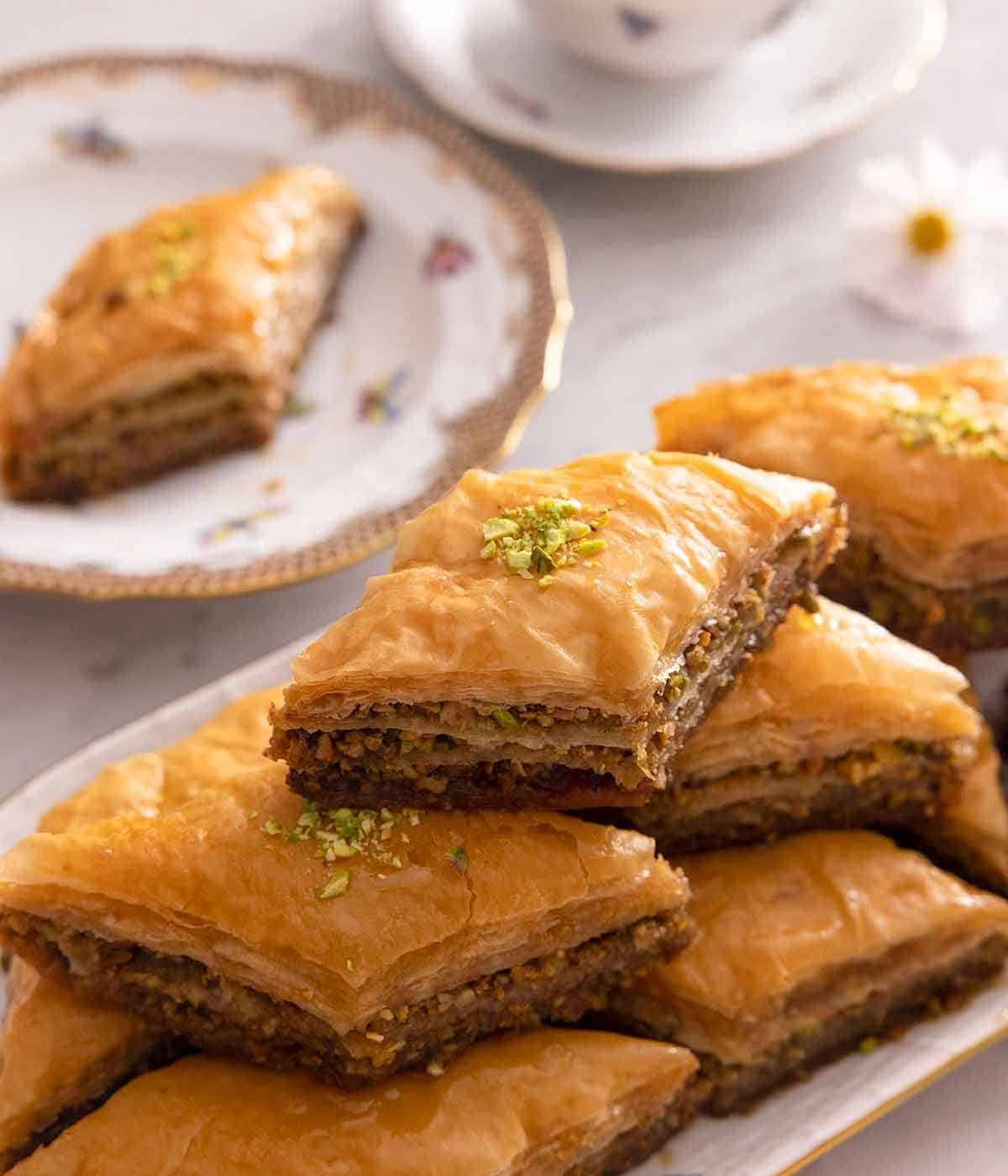 A platter of baklava stacked on top of each other with a plate with a single serving in the background.