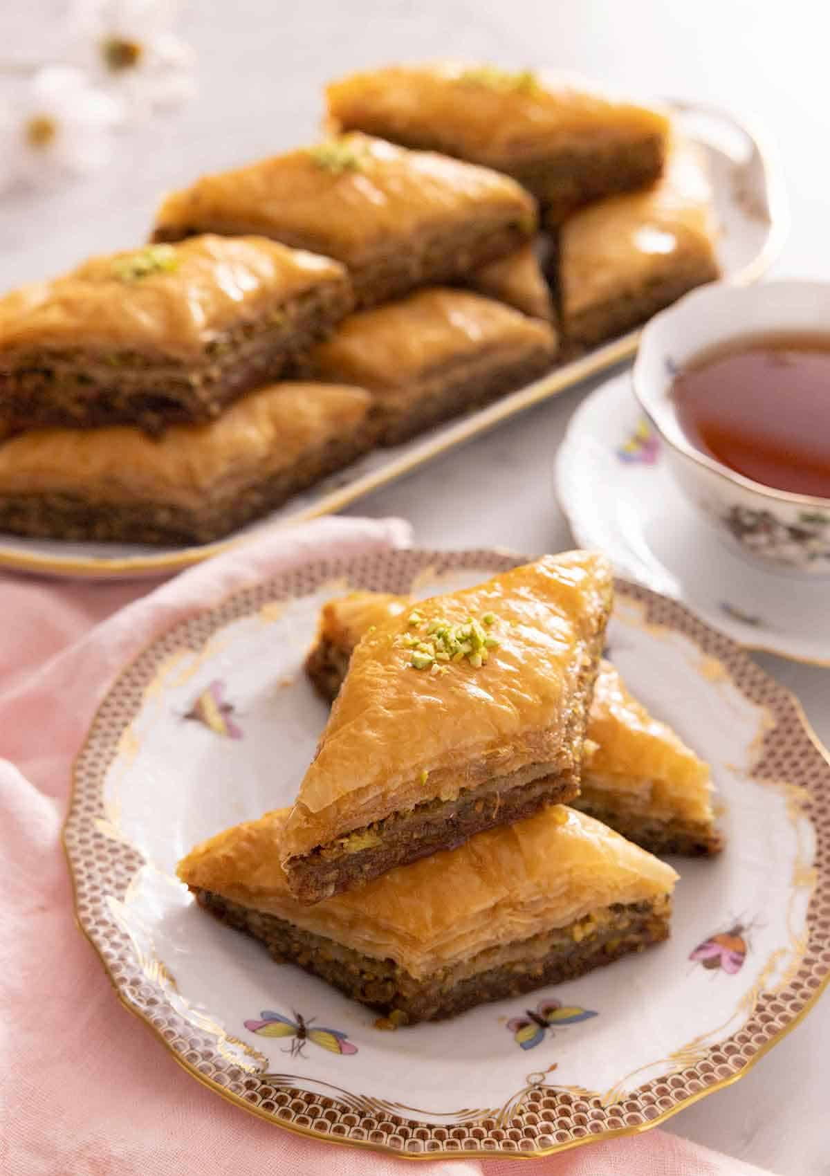 A plate with three baklava with one on top of two, with a platter of baklava in the background.