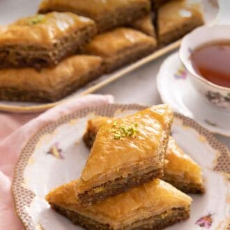Pinterest graphic of a plate with three baklava pieces with a platter in the back with a cup of tea.
