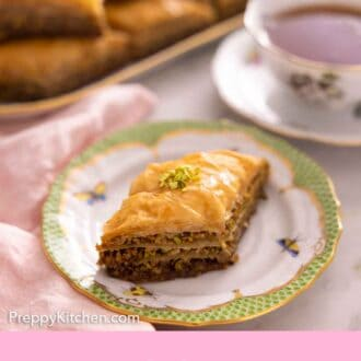 Pinterest graphic of a plate with a piece of baklava with a cup of tea and platter of more baklava out of focus in the background.
