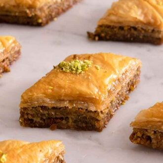 Multiple individual baklava pieces on a marble surface.