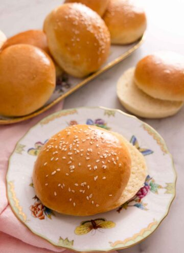 A plate with a brioche bun, sliced in half with more in the background on a platter.