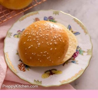 Pinterest graphic of a plate with a brioche bun with sesame seeds on top, sliced in half.