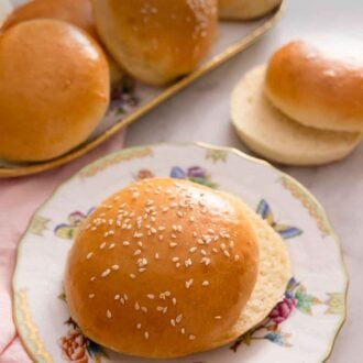 Pinterest graphic of a plate of brioche bun with sesame seeds on top with a platter of brioche buns in the background.