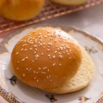 A brioche bun with sesame seeds on top, cut in half on a plate.