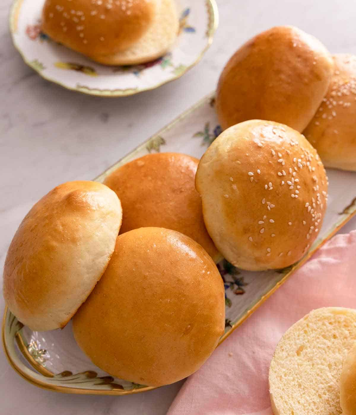 A serving platter of brioche buns with a couple of them topped with sesame seeds.