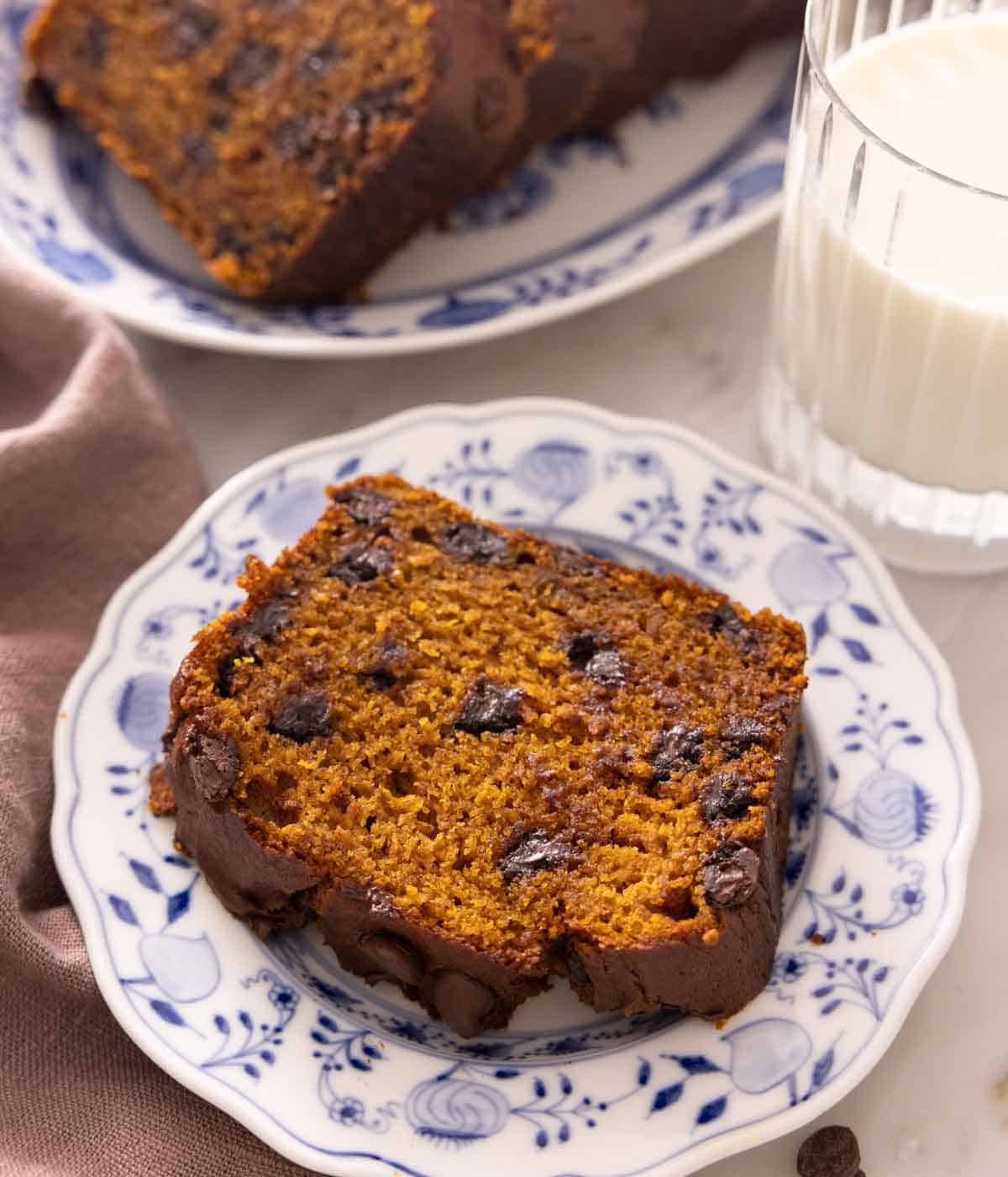 A slice of chocolate chip pumpkin bread on a plate with a cup of milk in the background.