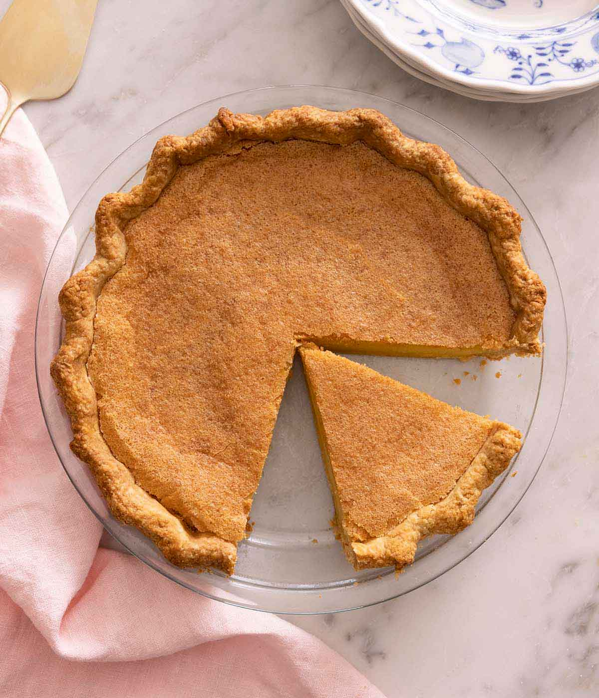 Overhead view of a chess pie in a pie dish with one slice removed and a cut slice in the dish.