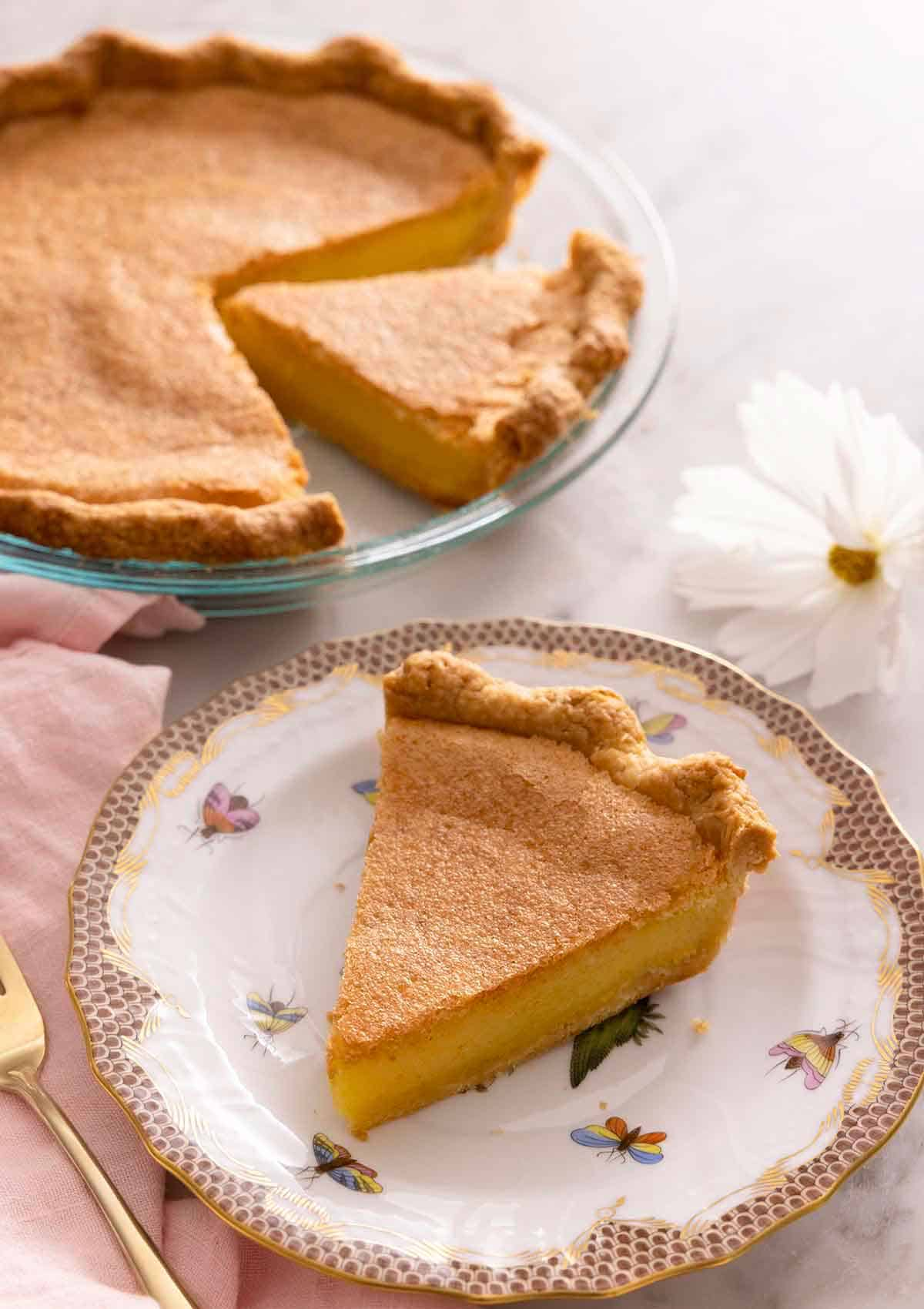 A slice of chess pie on a plate in front of the rest of the pie in the background.