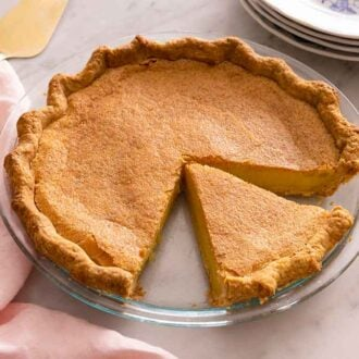 A chess pie in a glass pie dish with one slice cut out.