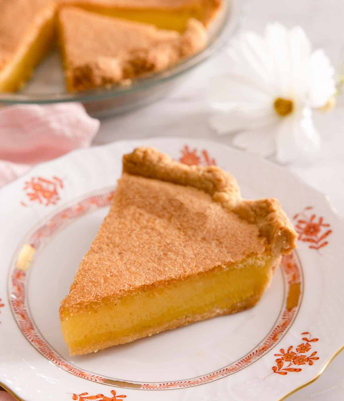A slice of chess pie on a white plate with orange floral print.