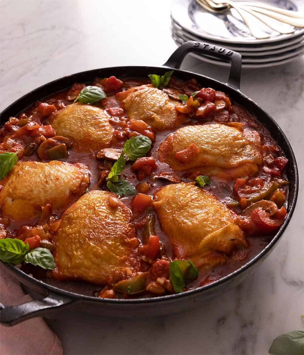 A large cast iron pan containing chicken cacciatore beside a stack of plates.