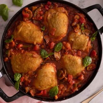 Overhead view of chicken cacciatore in a pan with a linen napkin and spoon beside it.