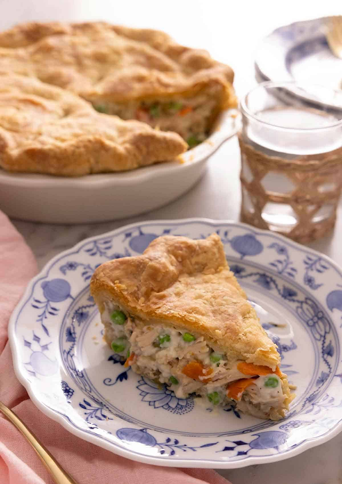 A plate of with a slice of chicken pot pie in front of a glass of water and the pie dish.