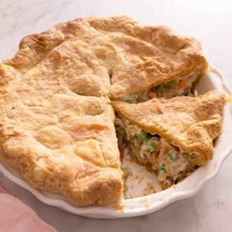 A chicken pot pie in the baking dish with some slices cut, beside a pink linen napkin.