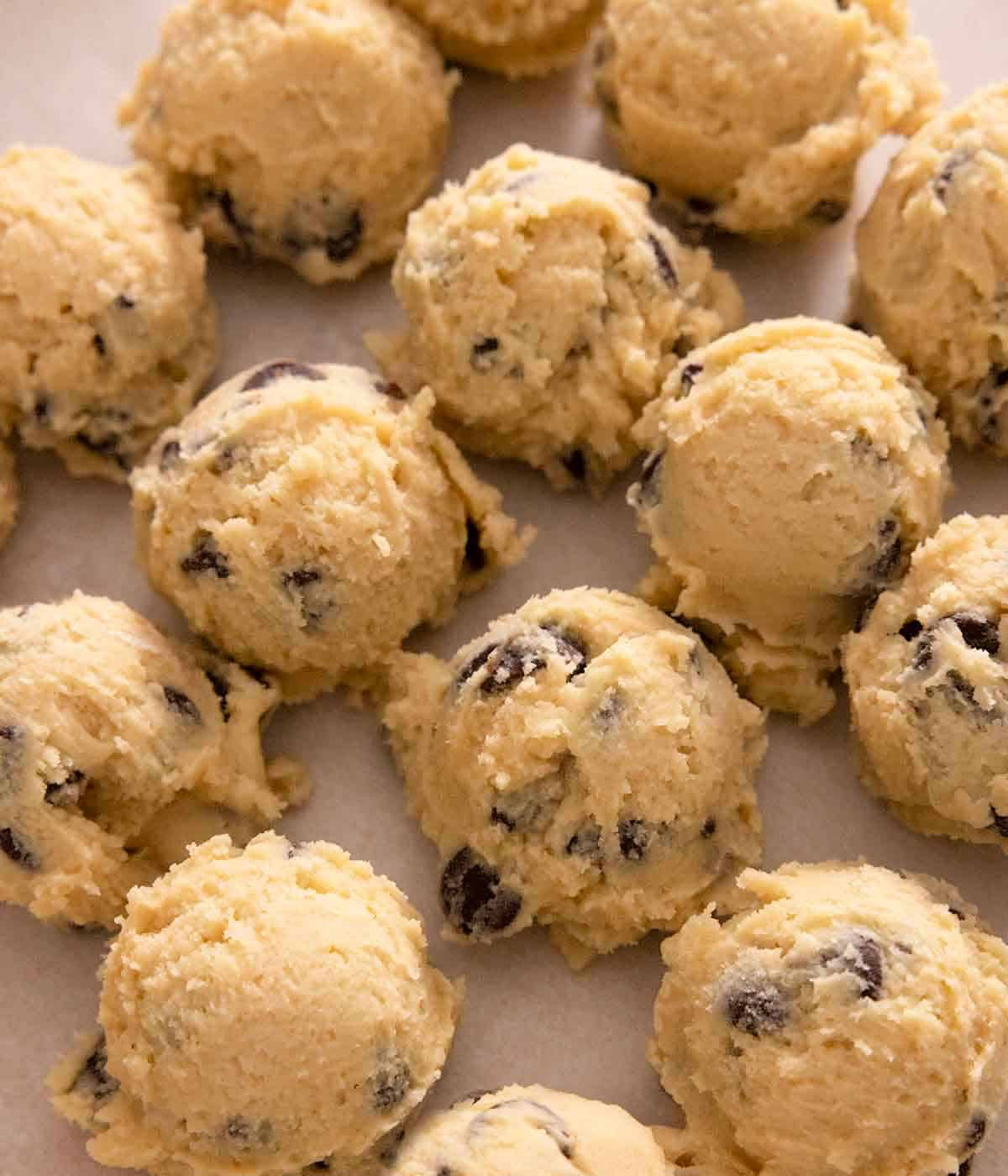 Multiple scoops of raw cookie dough on a lined sheet pan.