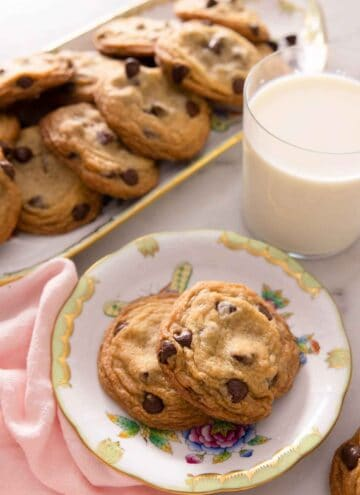 A plate with two chocolate chip cookies in front of a cup of milk and platter of cookies.