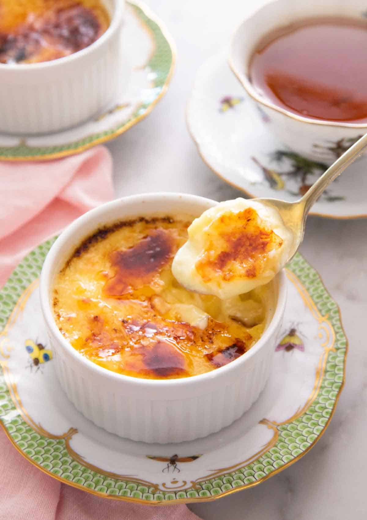 A spoonful of crème brûlée lifted from the ramekin with a cup of tea in the background.