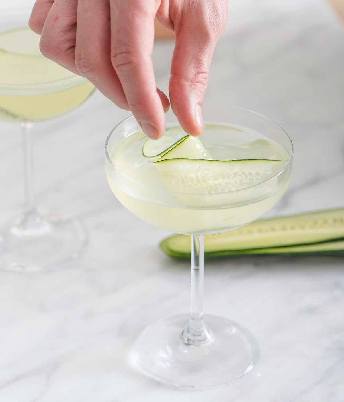 A hand placing in a sliced cucumber into a glass of cucumber martini.