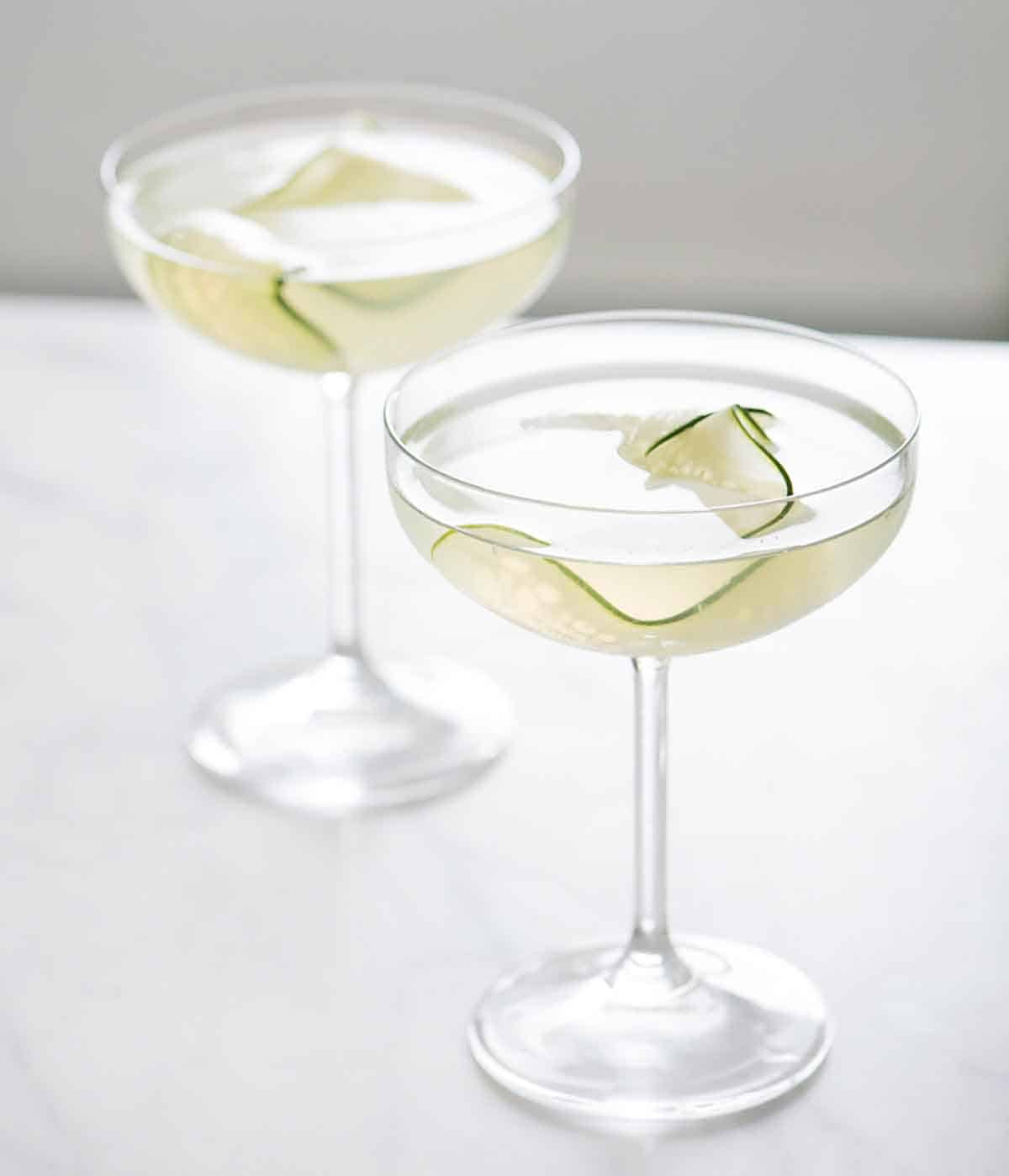 Two glasses of cucumber martini with sliced cucumber as garnish.