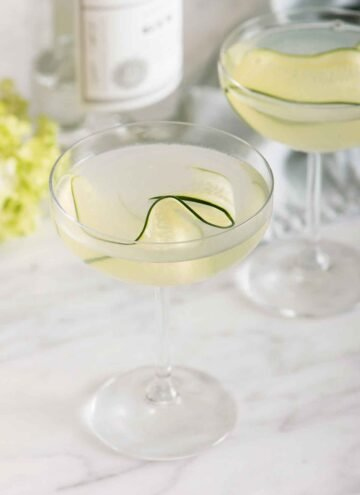 Two glasses of cucumber martini with one in front of the other. Both has a thin slice of cucumber as garnish.