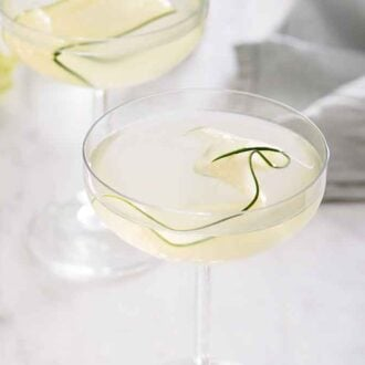 A glass of cucumber martini with a linen napkin in the background and a second martini out of focus.