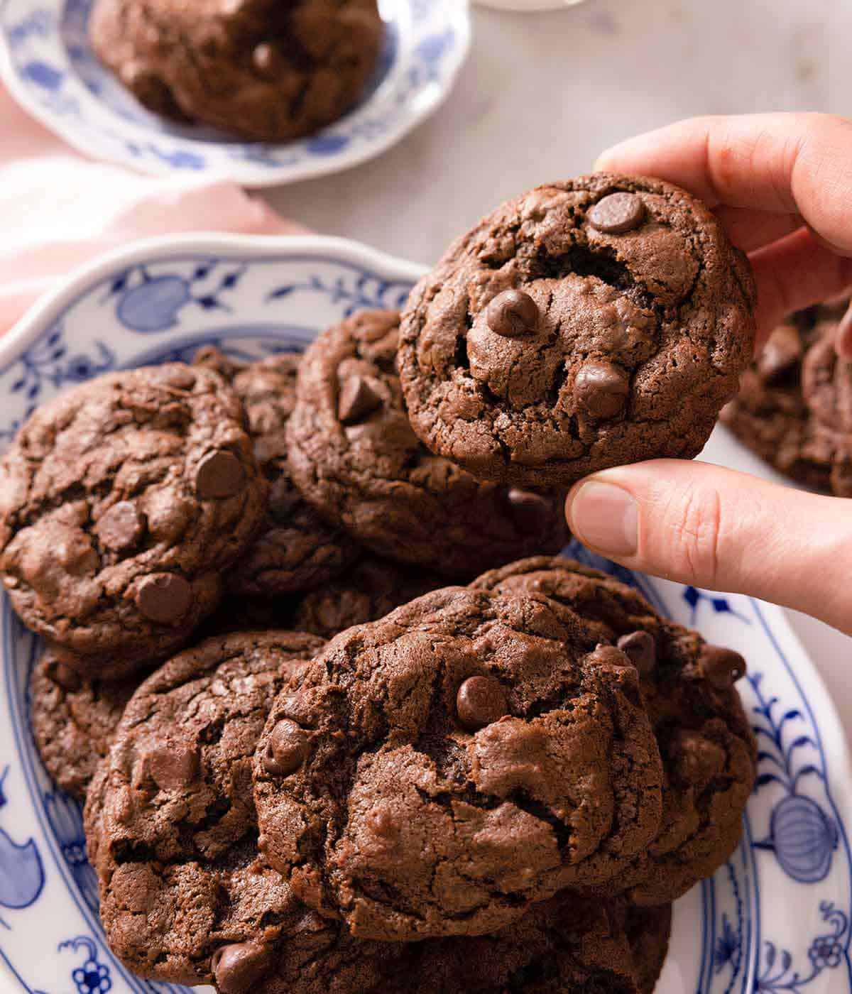 A hand lifting up a double chocolate chip from a platter of cookies.