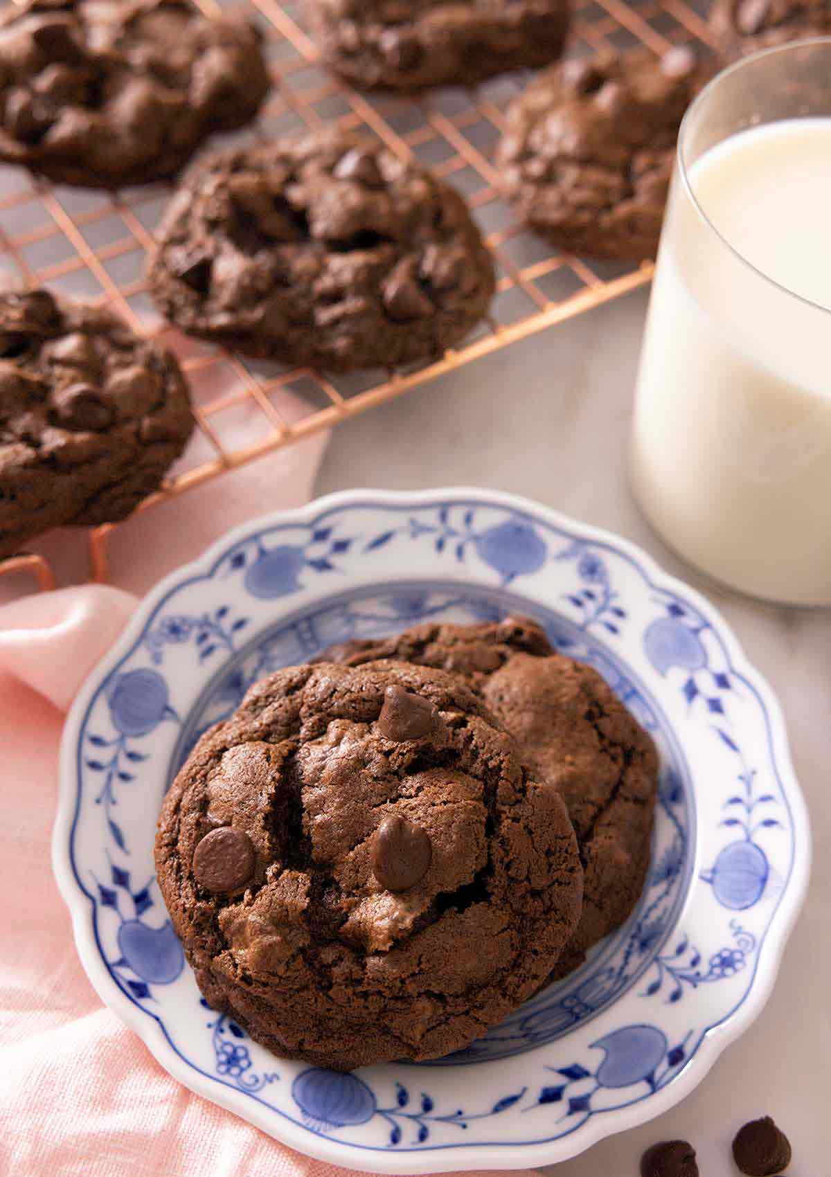 Two double chocolate chip cookies on a plate by a glass of milk with a cooling rack with more cookies in the background.