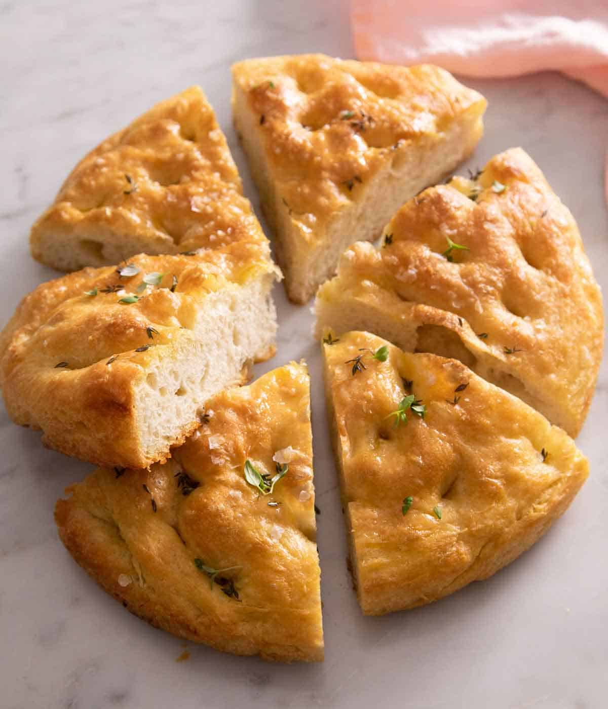 A round focaccia cut into 6 wedges on a marble surface.