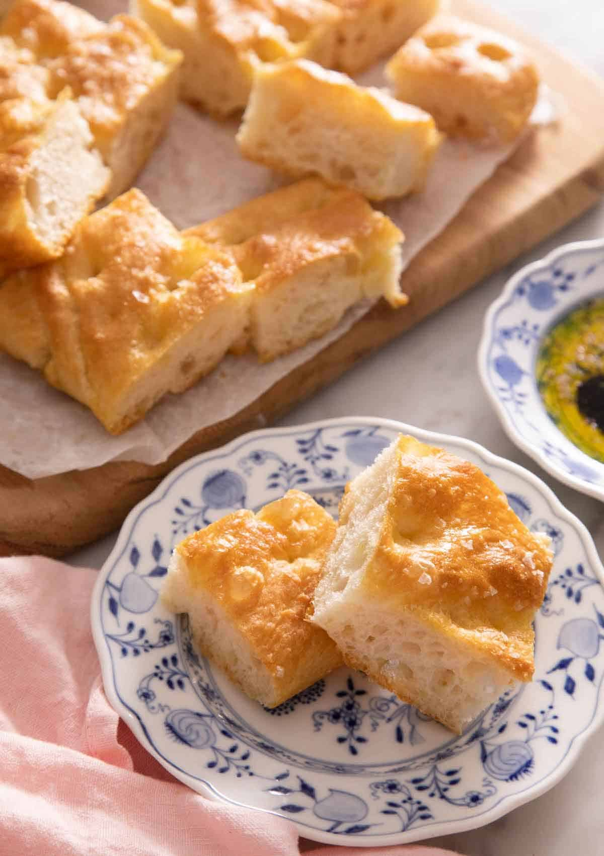 A plate with those pieces of focaccia in front of a cutting board with more pieces.