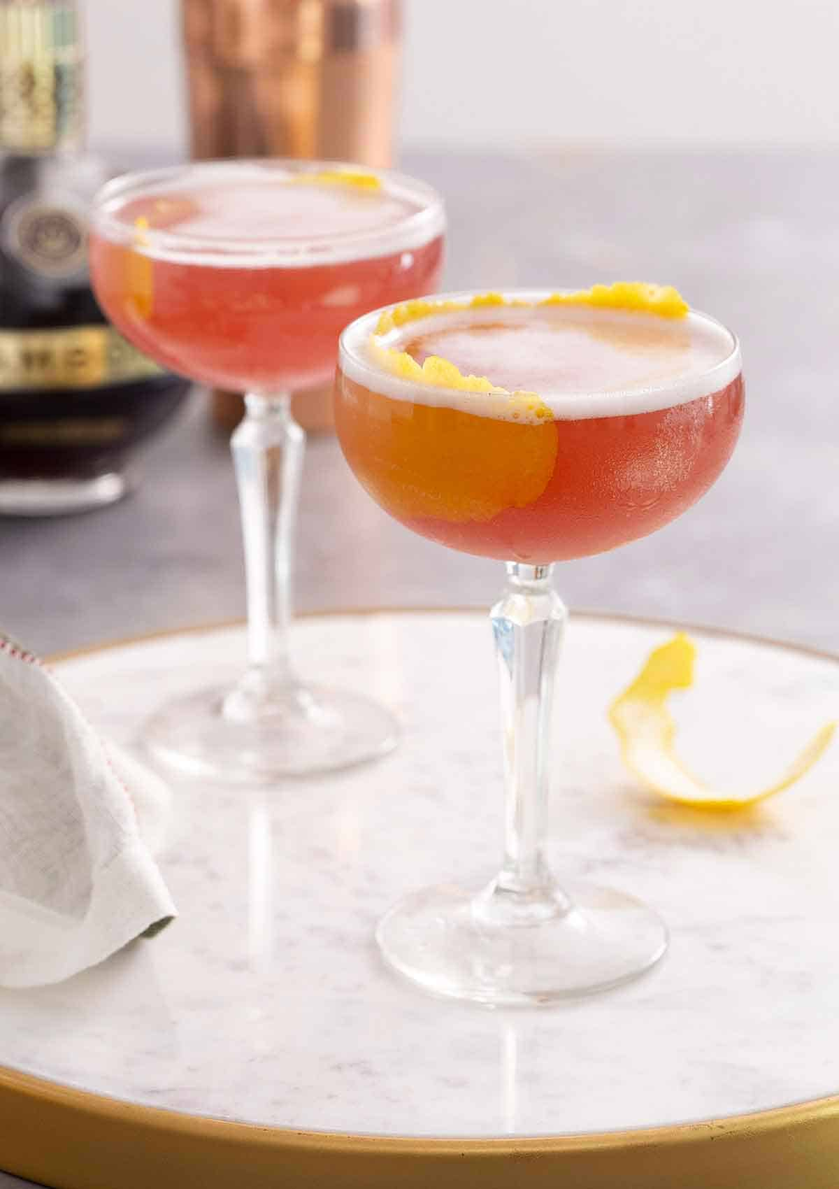 Two glasses of French martini with lemon garnish on a marble surface.