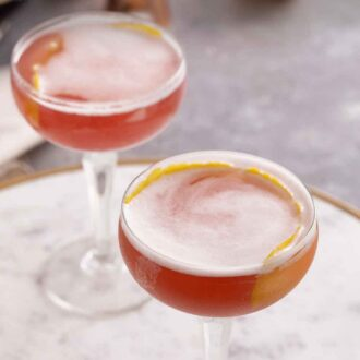 Pinterest graphic of an angled view of two glasses of French martinis, both with lemon peel garnishes.