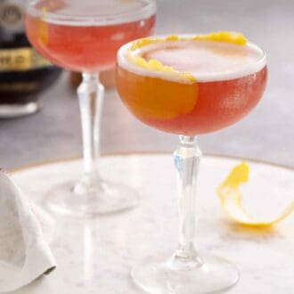 Pinterest graphic of two glasses of French martinis on a marble serving tray.