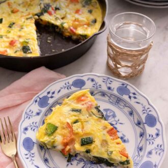 Pinterest graphic of a plate with a slice of frittata with a cast iron with the rest of the frittata in the background.