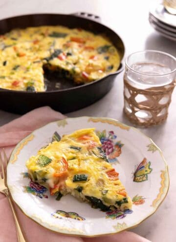 A plate with a slice of frittata with the skillet with the rest of the frittata in the background.