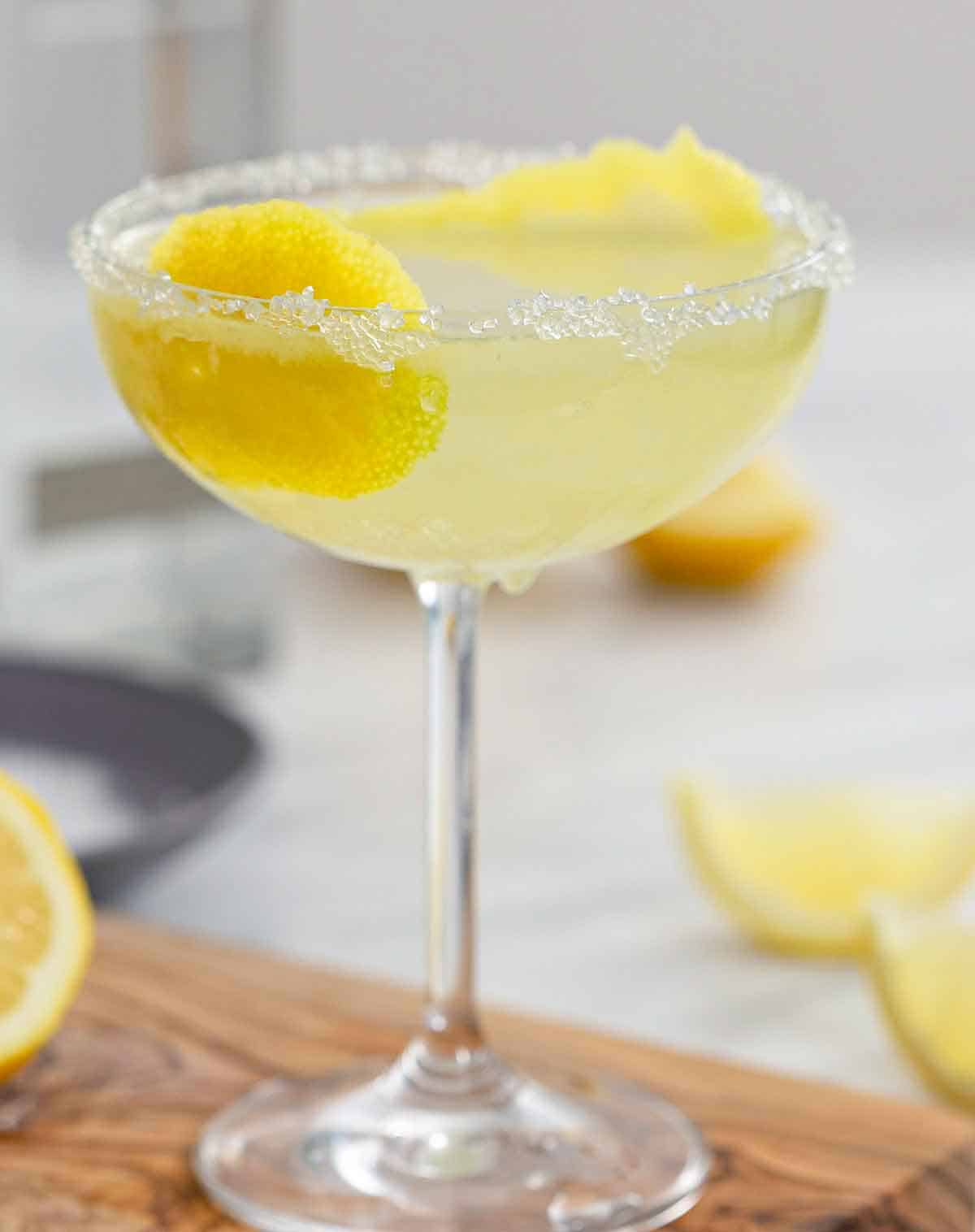 A lemon drop martini with sugar on the rim and lemon peel in the glass on a wooden cutting board.
