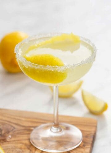A glass of lemon drop martini with a lemon peel in the glass and a sugared rim.