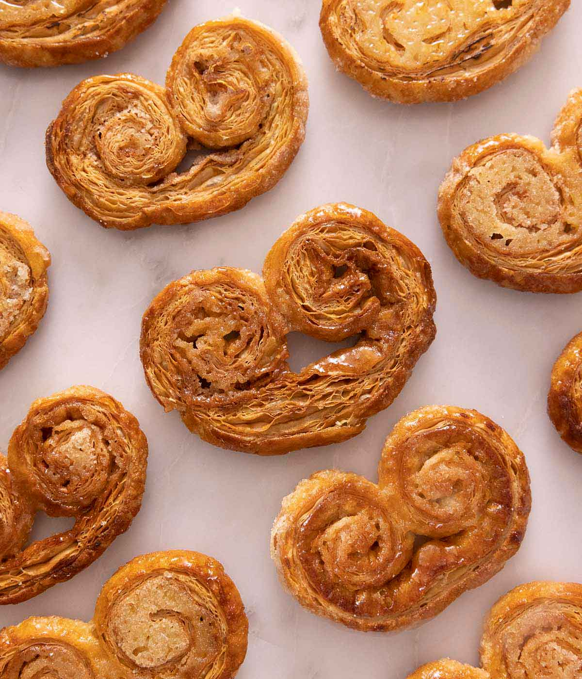 Multiple palmiers laid in a single layer on a marble surface.